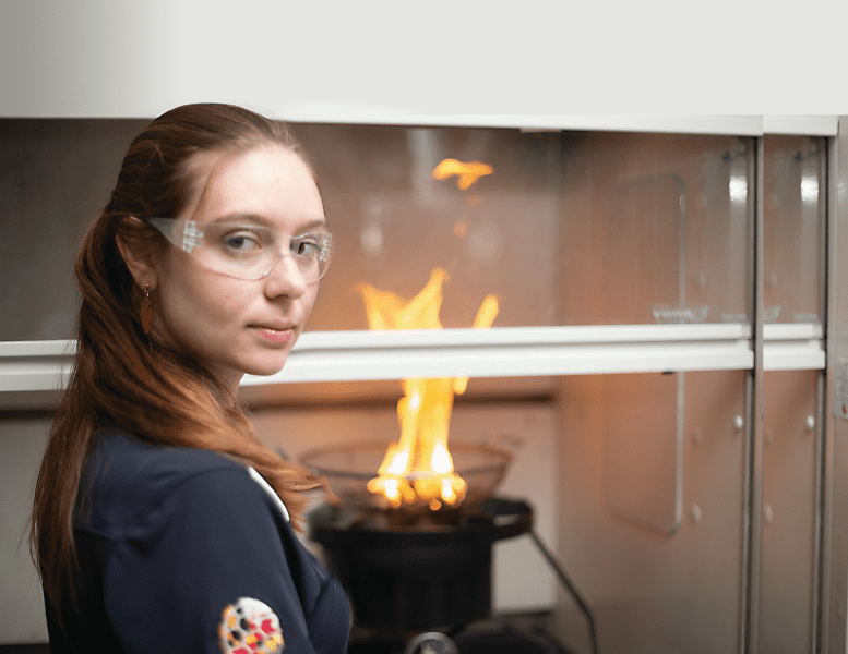 Raquel Hakes Weston-Dawkes stands in front of a flame in a science lab